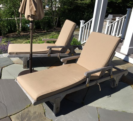 Pair of Teak Wood Chaise Lounges, with tan cushions, accompanied by a matching umbrella and teak side chair